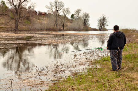 a man fishing on the Bank of the river on a fishing rod Banque d'images