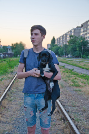 A young guy with a backpack and a dog in his hands on the street is on the railway selective focus