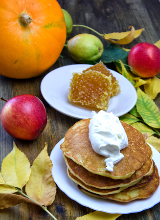 autumn leaves and red apples and pumpkin and pumpkin pancakes next to honey on a wooden table