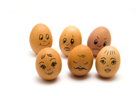 Eggs with painted emotions, psychology of society on a white background, selective focus