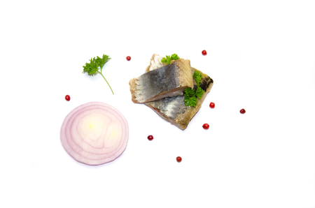 pieces of herring fish and a sprig of parsley and pepper and onion rings on a white background
