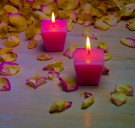 petals and burning pink candles on wooden background selective focus