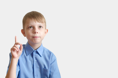 the boy looks up and points a finger on white background