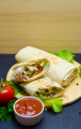 Shawarma with vegetables and chicken on a wooden background next to tomato ketchup and green leaves selective focus Foto de archivo - 120933090
