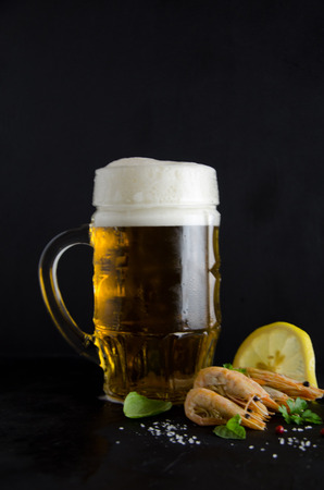 a mug of beer and a number of shrimp salt and lemon on a black background selective focus