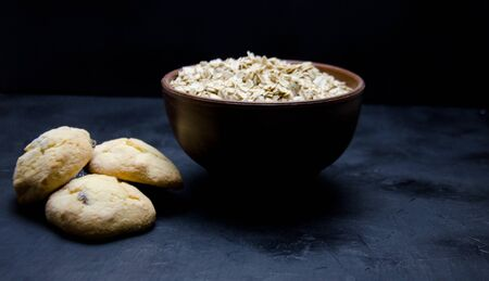 oatmeal cookies and a Cup of dry oatmeal on a black background blurred
