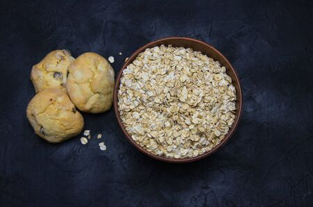 oatmeal cookies and a Cup of dry oatmeal on a black background blurred image Zdjęcie Seryjne