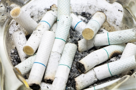 Dozen of Cigarette butt in an ashtray  photo