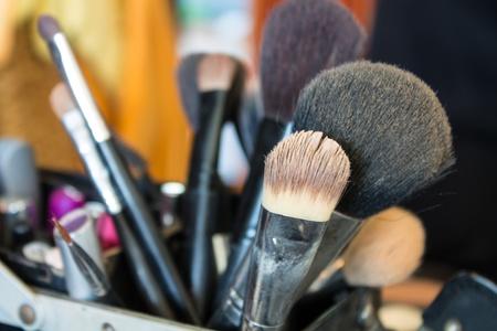 A bunch of make-up brushes lying randomly photo