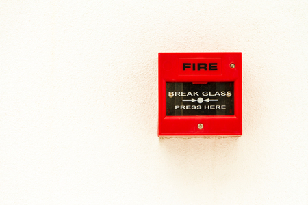 Red fire alarm switch on white concreat wall. photo