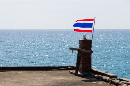 ethnical: Flag of Thailand on small pole in front of sea
