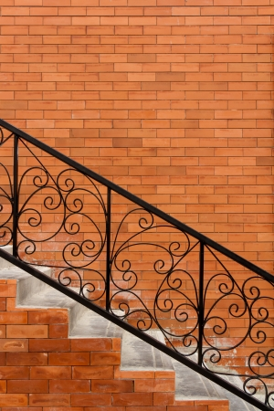 banister: Sloping concrete stair steps and steel handrail Stock Photo
