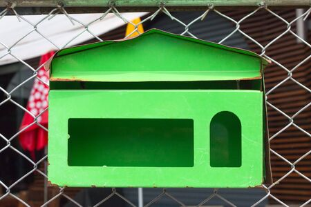 picket green: A plain green Mailbox  hanging on steel mesh