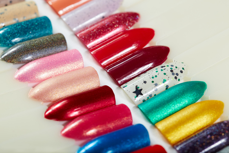 salon background: Artificial nails different colored with nail polish Stock Photo