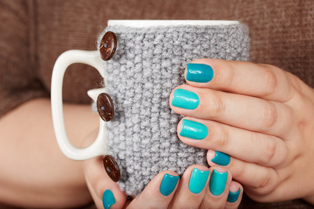 Hands with manicured nails holding a tea cup with knitted cover Stockfoto