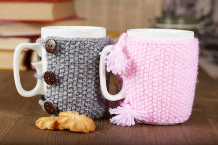 valentine day cup of coffee: Couple of tea cups with knitted covers and biscuits Stock Photo
