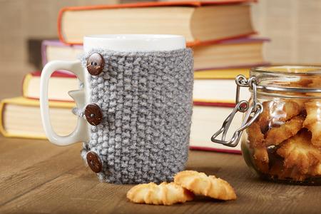 taza cafe: Taza de t� con la cubierta hecha a mano de punto, galletas, libros, mesa de madera Foto de archivo