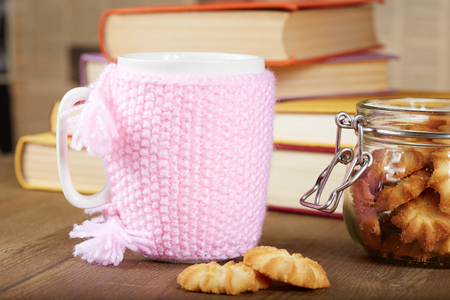 valentine day cup of coffee: Tea cup with handmade knitted cover, biscuits, books, wooden table