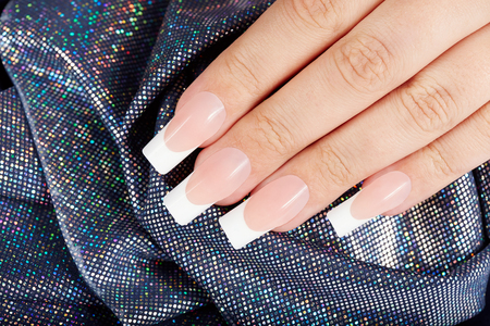 nails woman: Hand with long artificial french manicured nails