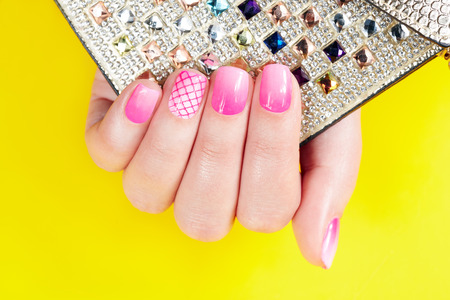 artificial nails: Nails with manicure covered with pink nail polish, yellow background
