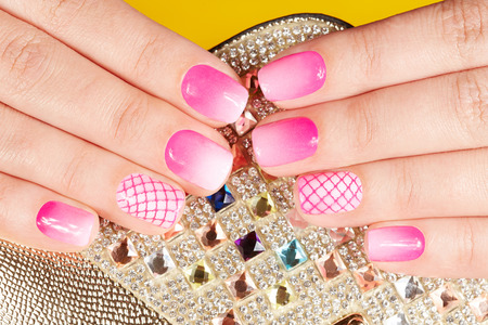 artificial nails: Hands with manicured nails covered with pink nail polish Stock Photo