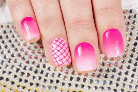 Nails with manicure covered with pink nail polish on crystals background