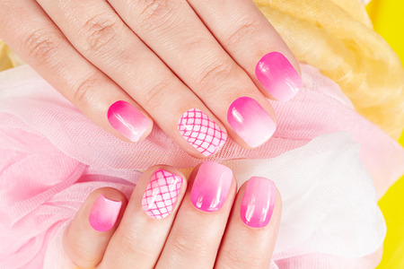 Hands with manicured nails covered with pink nail polish Фото со стока