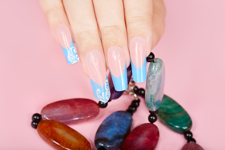 artificial nails: Hand with long artificial french manicured nails holding a necklace