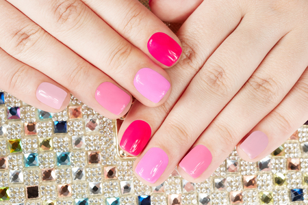 artificial nails: Hands with manicured nails on colorful crystals background
