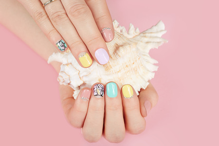 Hands with manicured nails different colored with nail polish and sea shell Фото со стока