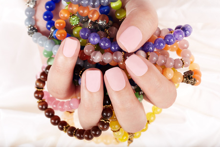 Hand with beige matte manicured nails and colorful bracelets Stock Photo