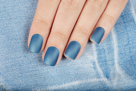cat eye: Hand with blue matte manicured nails on jeans textile background Stock Photo