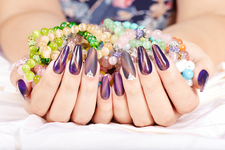 Hands with long artificial manicured nails holding colorful bracelets Stockfoto