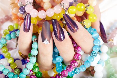 Hand mit langen künstlichen manikürten Nägeln bunten Armbänder halten