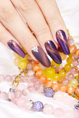 artificial nails: Hand with long artificial manicured nails holding a necklace