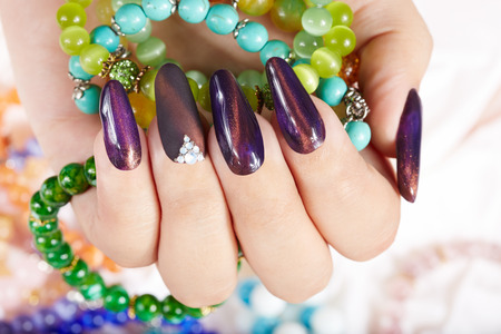 artificial nails: Hands with long artificial manicured nails holding colorful bracelets Stock Photo