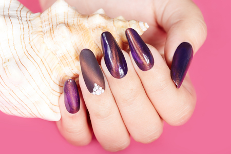 artificial nails: Hand with long artificial manicured nails and seashell Stock Photo