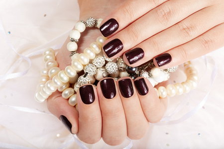 Hands with short manicured nails colored with dark purple nail polish holding necklaces