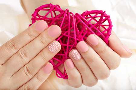 Hands with pink matte manicured nails holding a heart
