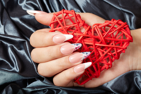 Hand with long artificial french manicured nails holding a heart Stock Photo