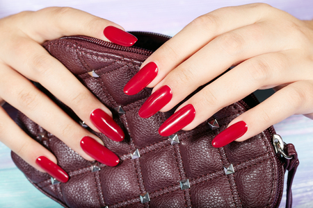 Hands with long artificial manicured nails colored with red nail polish holding a handbag