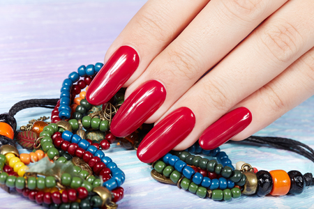 Hand with long artificial manicured nails colored with red nail polish