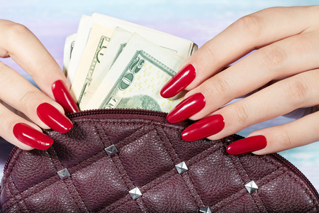 Hands with long artificial manicured nails colored with red nail polish taking out money from the handbag