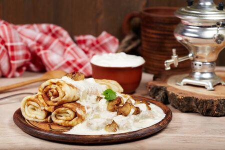 Pancakes with meat, mushrooms and sour cream sauce. Traditional Russian cuisine. Maslenitsa. Stock Photo