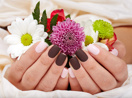 Hands with pink and purple manicured nails holding a bouquet of flowers Archivio Fotografico