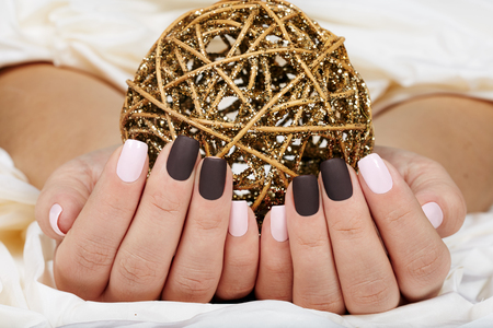 Hands with manicured nails colored with pink and purple nail polish holding a golden ball