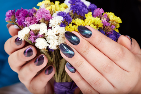 Hands with manicured nails with cat eye design holding a bouquet of flowers