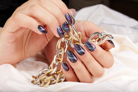 Hands with manicured nails with cat eye design holding a necklace Archivio Fotografico