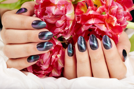 Hands with manicured nails with cat eye design holding pink tulip flower