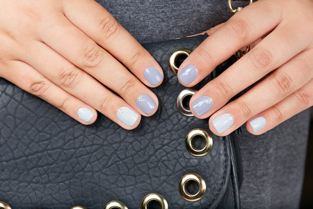 Hands with short manicured nails colored with gray nail polish